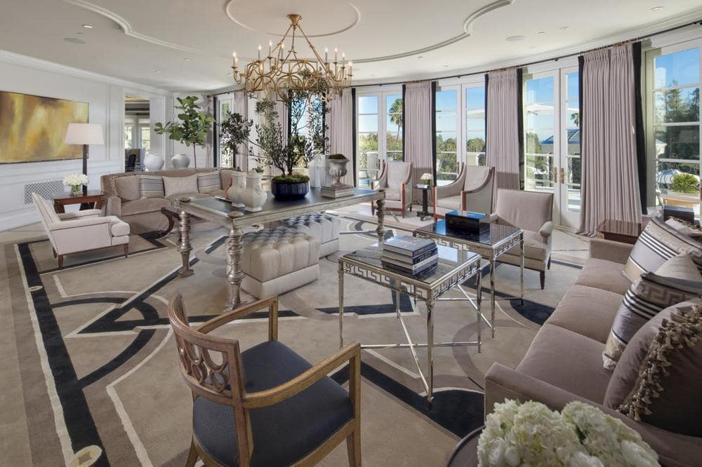 This is a closer look at the living room sofas, armchairs and glass-top coffee tables under a large white ceiling with a chandelier in the middle. Image courtesy of Toptenrealestatedeals.com.