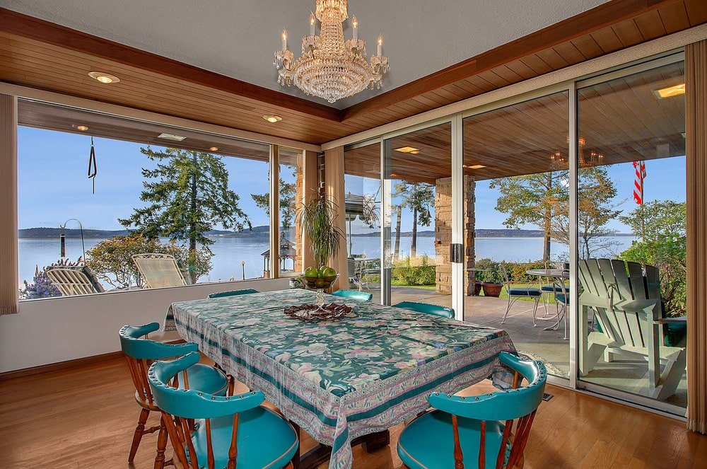 This is the dining room with a rectangular dining table surrounded by green wooden chairs and surrounded by glass walls. Image courtesy of Toptenrealestatedeals.com.