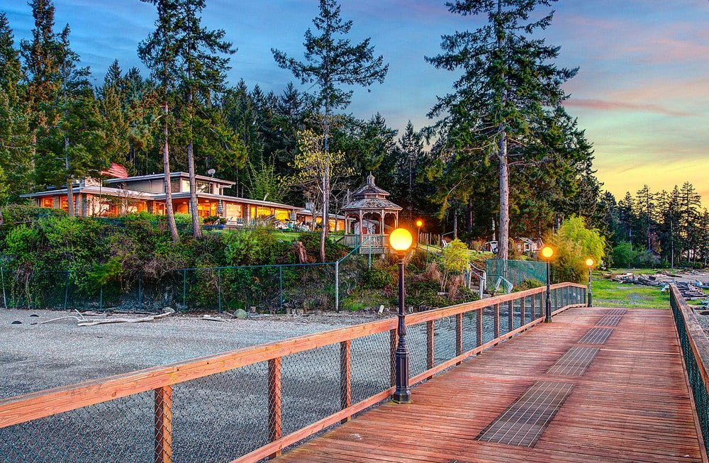 This is the wooden walkway leading to the dock with wooden railings and outdoor lighting on the side. Image courtesy of Toptenrealestatedeals.com.