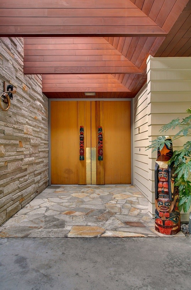 This is the main entrance with wooden double doors. These are adorned with a couple of colorful tiki posts that serve as handles. Image courtesy of Toptenrealestatedeals.com.