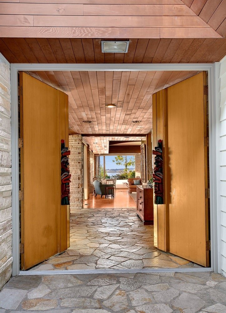 The wooden double doors open to the foyer that has a mosaic stone flooring and a waist-high cabinet on the side. Image courtesy of Toptenrealestatedeals.com.