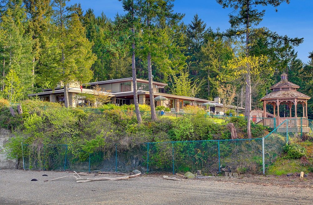 This is a view of the house from the vantage of the beach. You can see here the house complemented by the tall trees. Image courtesy of Toptenrealestatedeals.com.
