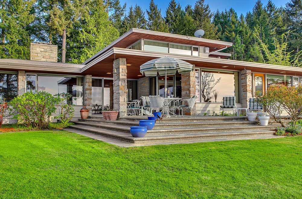 This is a look at the back of the house where you can see the glass walls, stone pillars and an outdoor dining set on the elevated patio adorned with potted plants. Image courtesy of Toptenrealestatedeals.com.