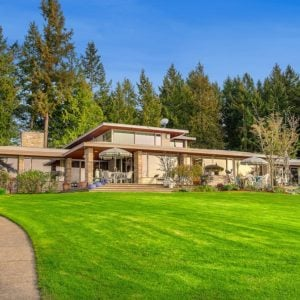 This is a look at the prairie-style house with lots of huge glass windows to better maximize the view. This is then complemented by a large grass lawn and the background of tall trees. Image courtesy of Toptenrealestatedeals.com.