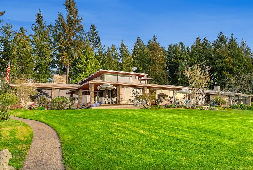 This is a look at the prairie-style house with lots of huge glass windows to better maximize the view. This is then complemented by a large grass lawn and the background of tall trees.