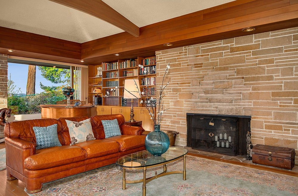This is the family room with a large stone wall housing the fireplace and a built-in bookshelf beside the brown leather sofa. Image courtesy of Toptenrealestatedeals.com.