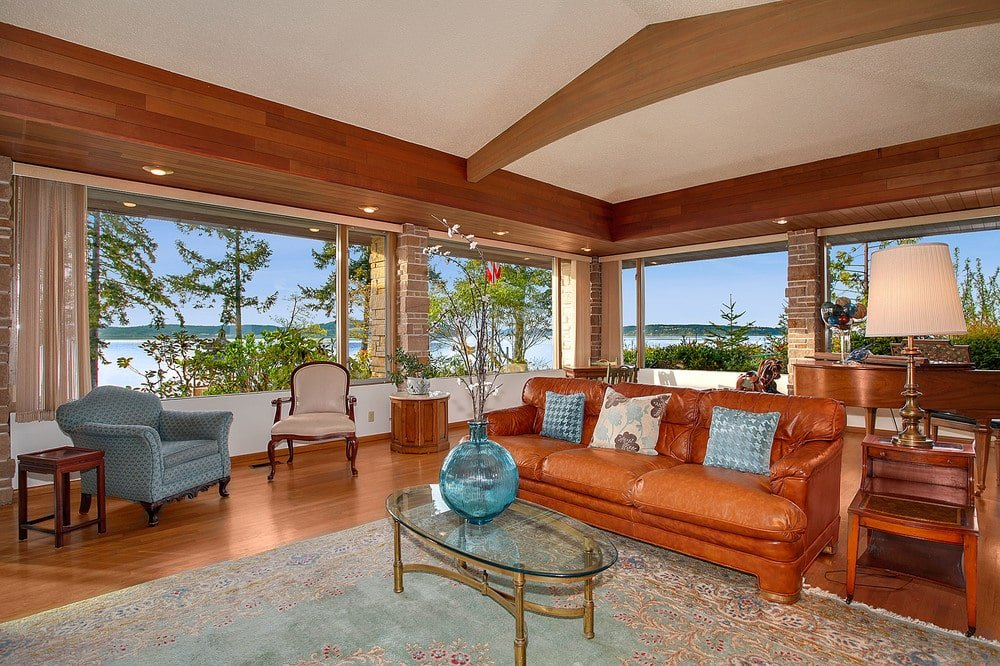 This other view of the family room showcases the large windows that give a view of the landscape outside. Image courtesy of Toptenrealestatedeals.com.