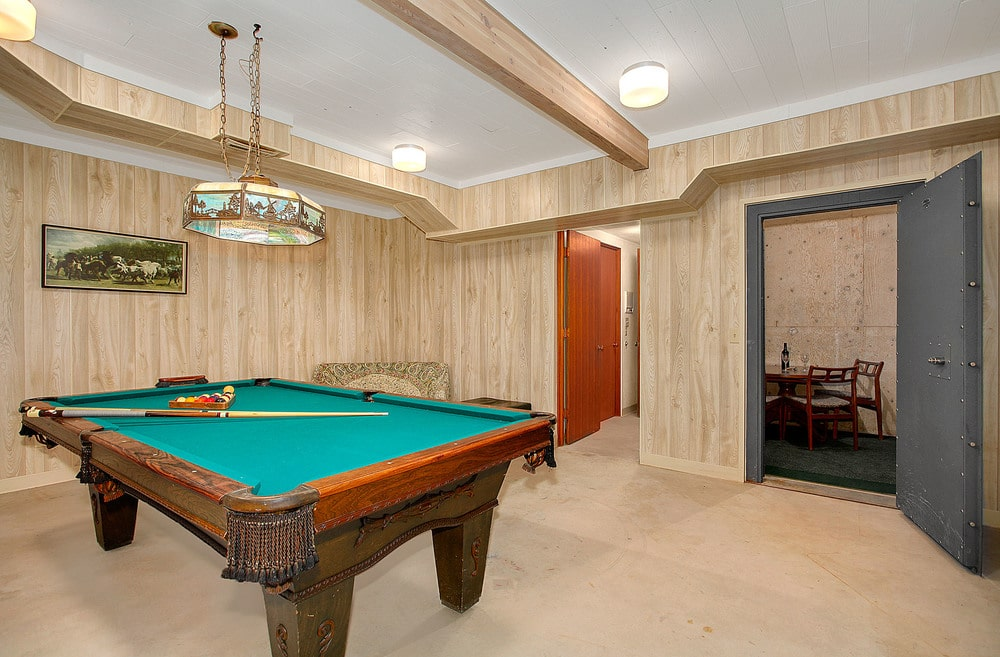 This is a look at the game room fitted with a large wooden pool table with green carpet topped with a drum pendant lighting. Image courtesy of Toptenrealestatedeals.com.