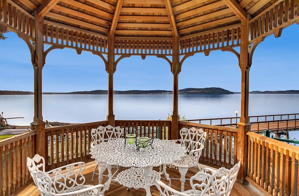 This is a look inside the wooden gazebo by the docks. This is fitted with an outdoor white dining set that stands out against the wooden tones. Image courtesy of Toptenrealestatedeals.com.