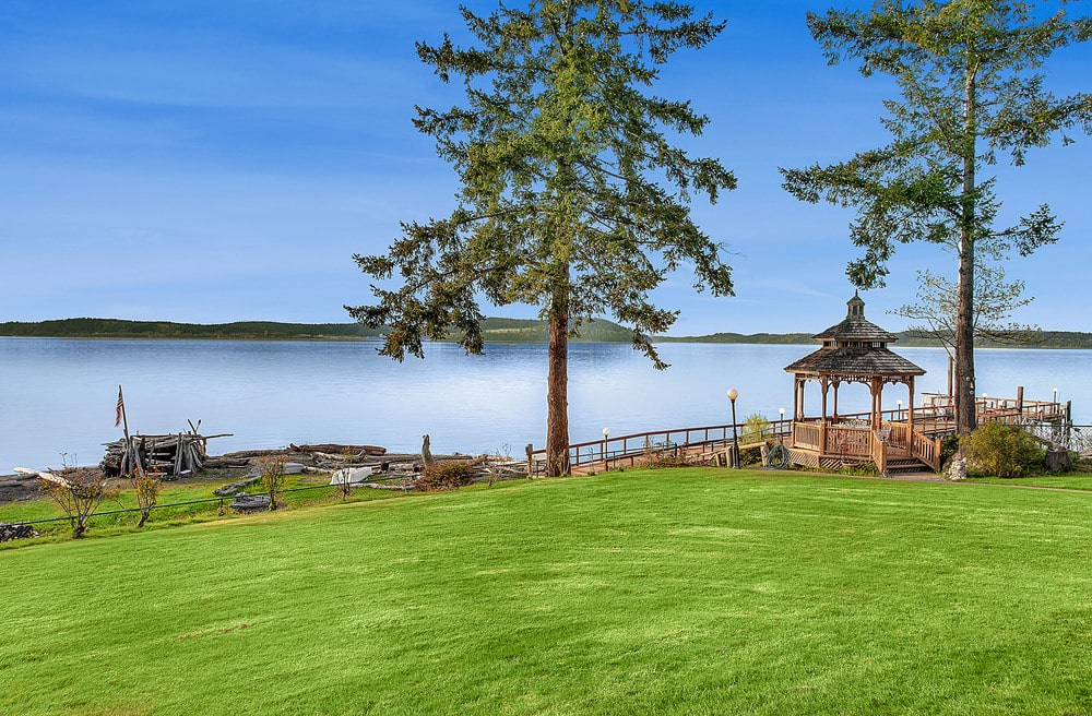 This is a look at the landscaping of the the back of the house facing the ocean. Here you can see a large grass lawn leading to the docks. Image courtesy of Toptenrealestatedeals.com.