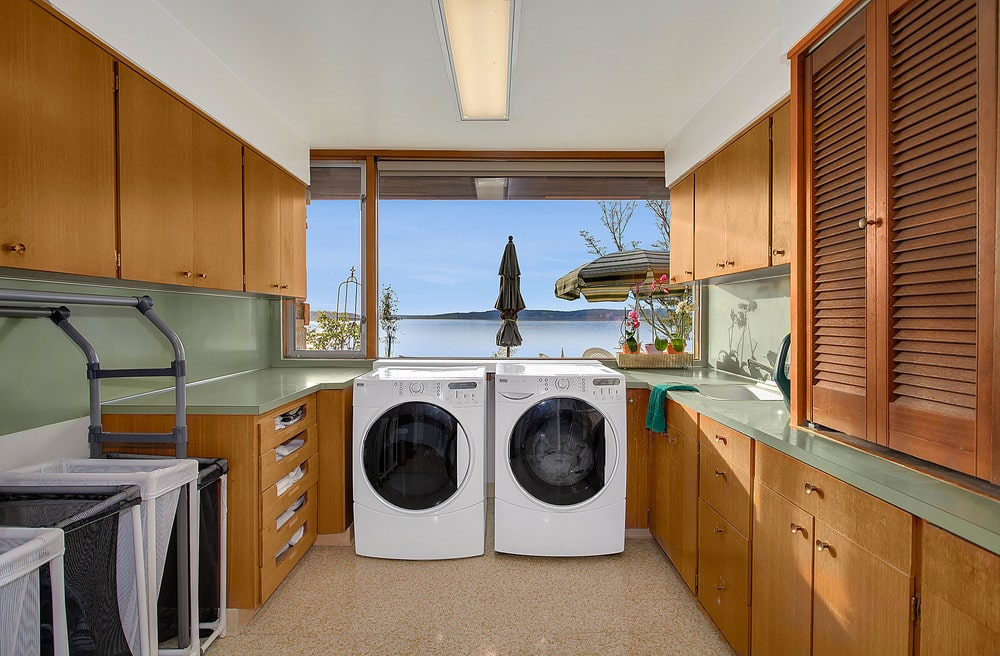 The laundry room has brown wooden cabinetry that makes the white modern appliances stand out. Image courtesy of Toptenrealestatedeals.com.