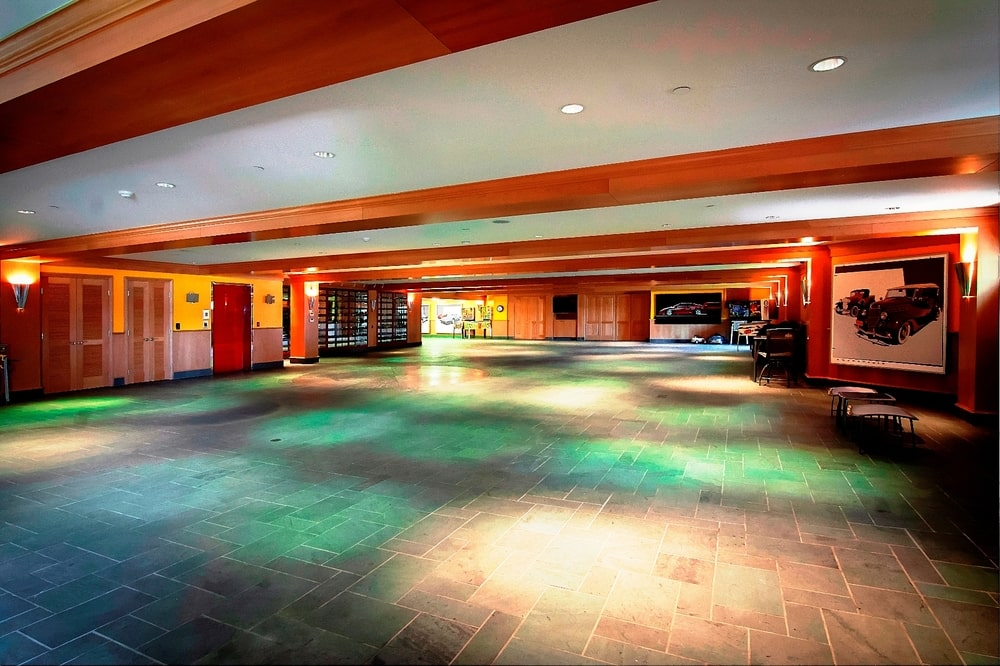 This is the spacious car showroom with a turntable and a large ceiling with exposed wooden beams. Image courtesy of Toptenrealestatedeals.com.