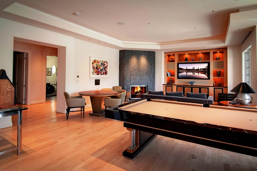 This is the den and game room with a large black pool table that stands out against the hardwood flooring. Image courtesy of Toptenrealestatedeals.com.