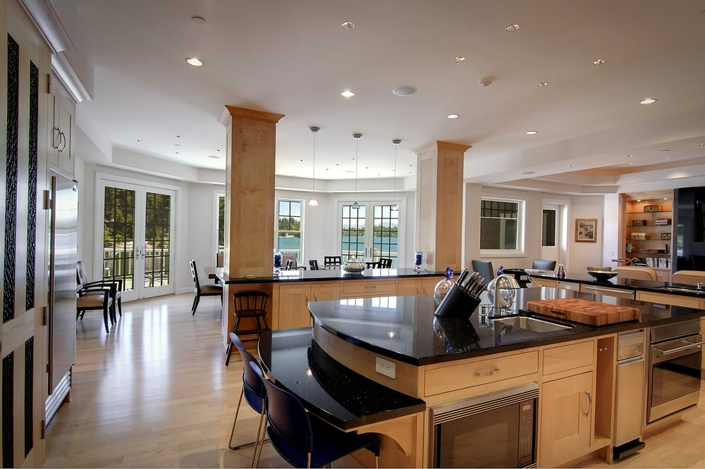 This is the kitchen with kitchen islands that have beige pillars. You can also see here the dining area at the far side by the windows. Image courtesy of Toptenrealestatedeals.com.