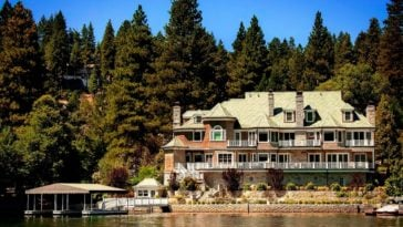 This is a view of the mansion from the vantage of the lake. Here you can see the exteriors of the house as well as the boathouse with a background of tall trees. Image courtesy of Toptenrealestatedeals.com.