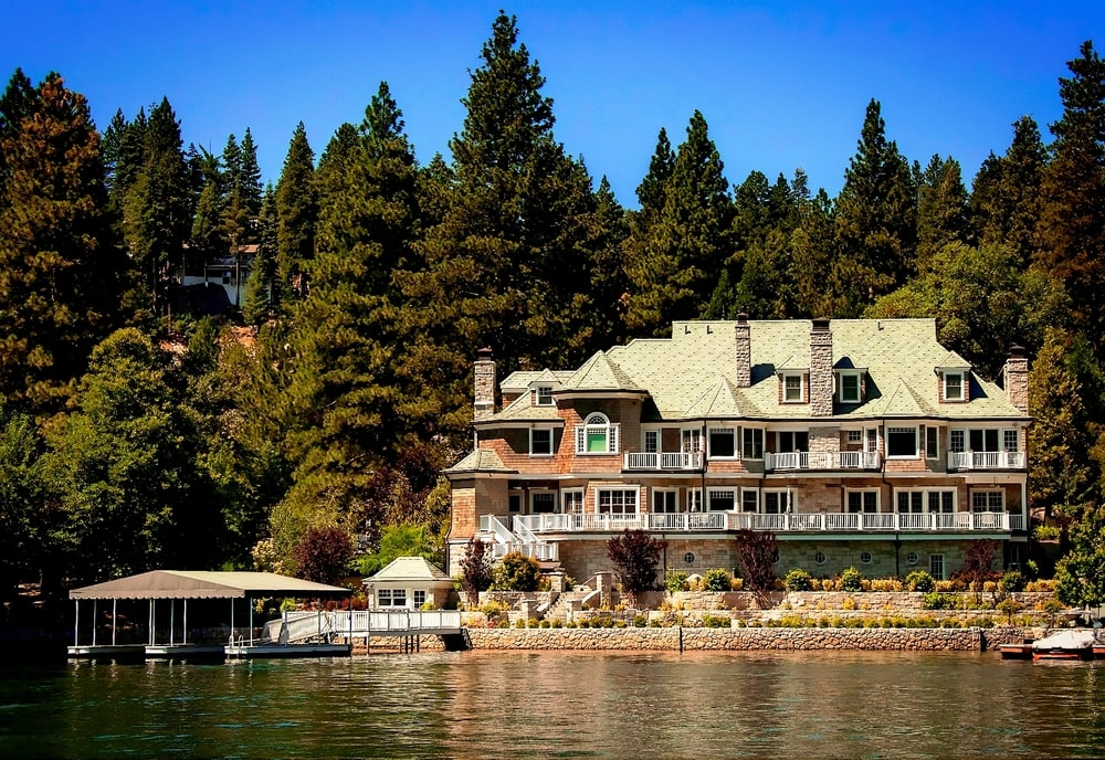 This is a view of the mansion from the vantage of the lake. Here you can see the exteriors of the house with balconies and dormer windows as well as the boathouse with a background of tall trees. Image courtesy of Toptenrealestatedeals.com.