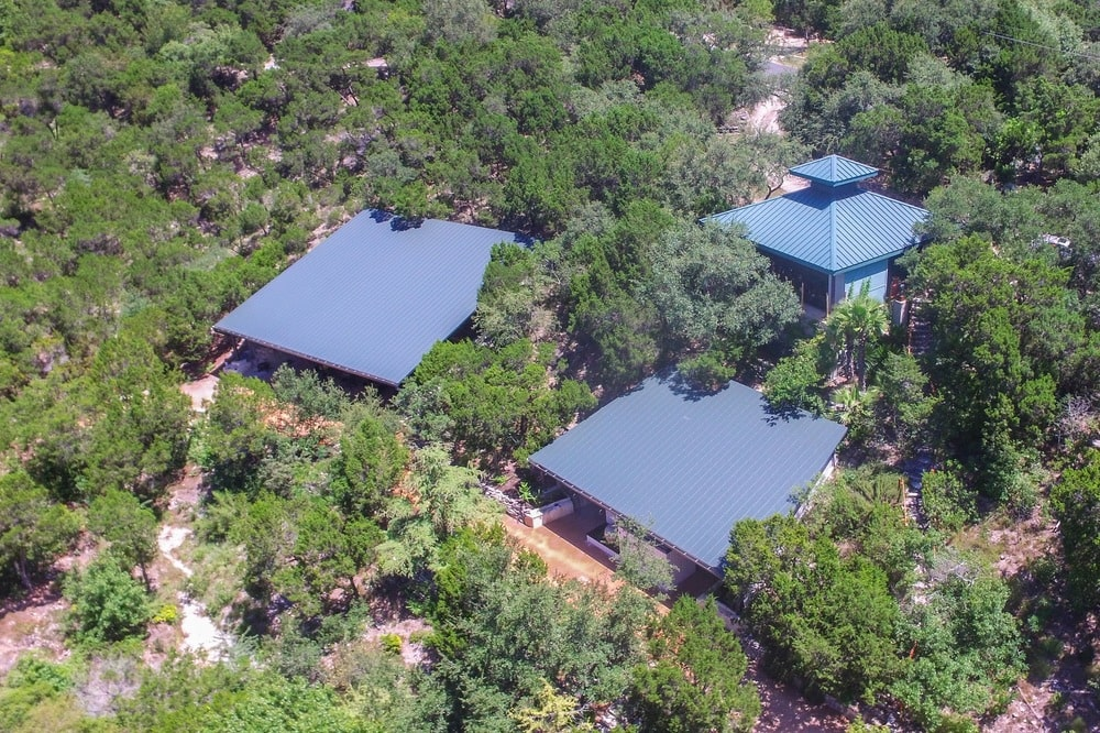 This aerial view of the estate shows the three separate building with gray roofs to stand out against the surrounding green landscape filled with tall trees. Image courtesy of Toptenrealestatedeals.com.