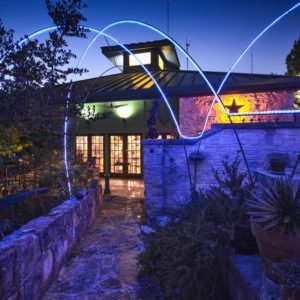 This is a front view of the house with large glass doors and stone exterior walls and walkways. These are then complemented by the colorful outdoor lighting. Image courtesy of Toptenrealestatedeals.com.
