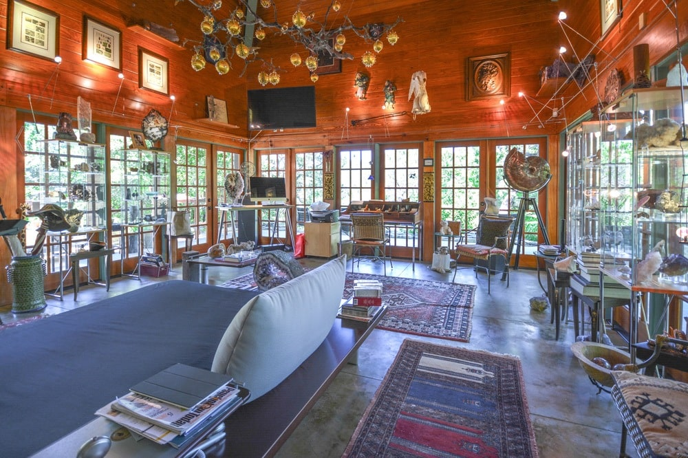 This is a look at the interior living room that is surrounded by glass walls and topped with a vibrant red ceiling filled with decors and lights. Image courtesy of Toptenrealestatedeals.com.
