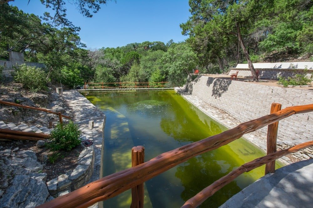 This is a look at the water scenery of the estate with a wooden bridge crossing it. Image courtesy of Toptenrealestatedeals.com.