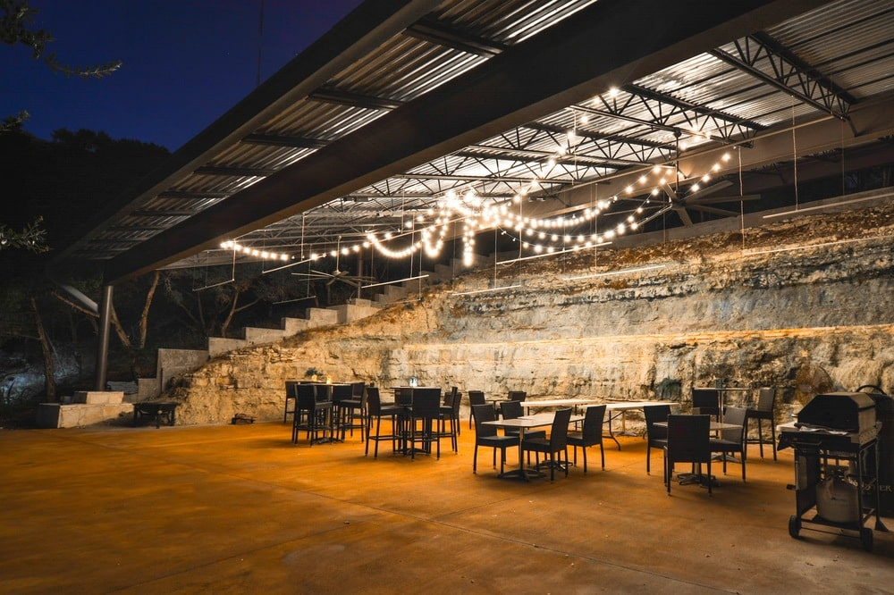 This is a large covered area fitted with multiple tables and chairs adorned with rope lights that cast a warm tone to the stone walls. Image courtesy of Toptenrealestatedeals.com.