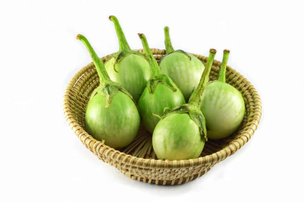 Little green eggplants in a round basket.