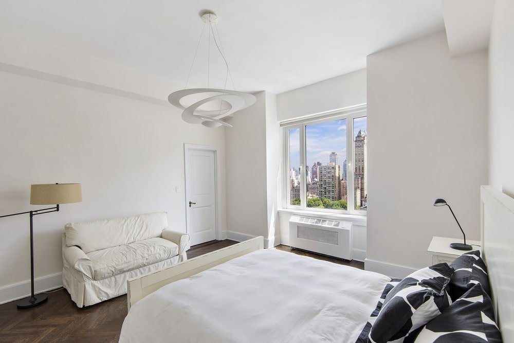 This other bedroom has a beige couch at the foot of the bed that is topped iwth a white decorative lighting. Image courtesy of Toptenrealestatedeals.com.