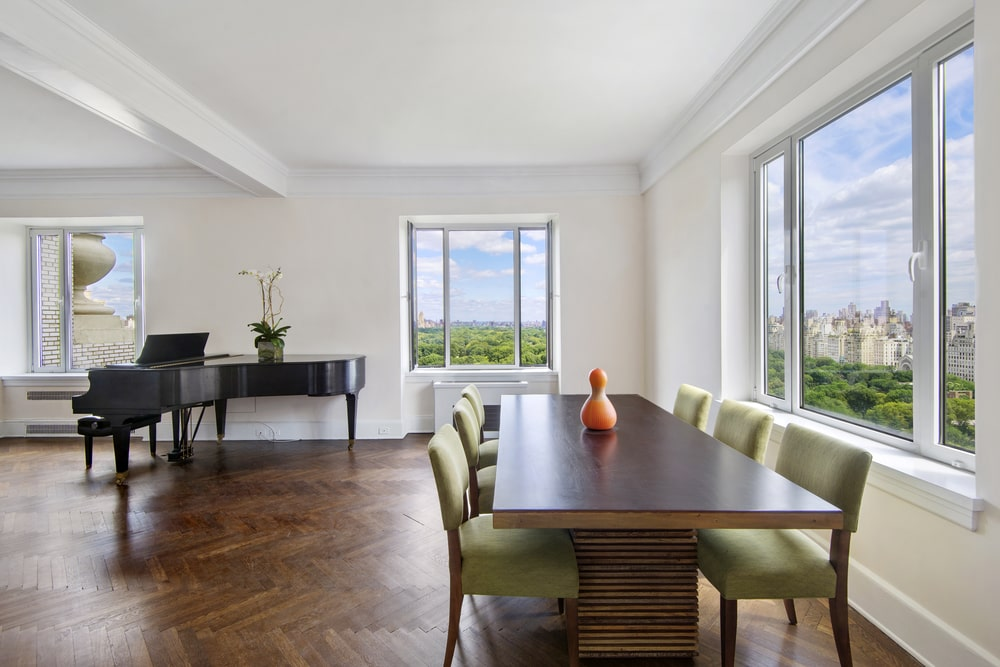 This is a closer look at the dining area of the great room. It has a rectangular wooden dining table surrounded green cushioned chairs by the wide windows. Image courtesy of Toptenrealestatedeals.com.