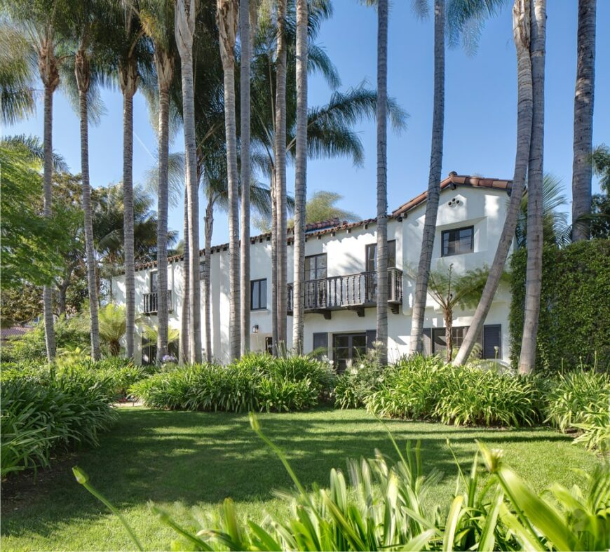 This is a view of the back of the house that has red tiles on its roof and white exterior walls with balconies and windows. These are then complemented by the tall tropical trees, shrubs and grass lawn. Image courtesy of Toptenrealestatedeals.com.