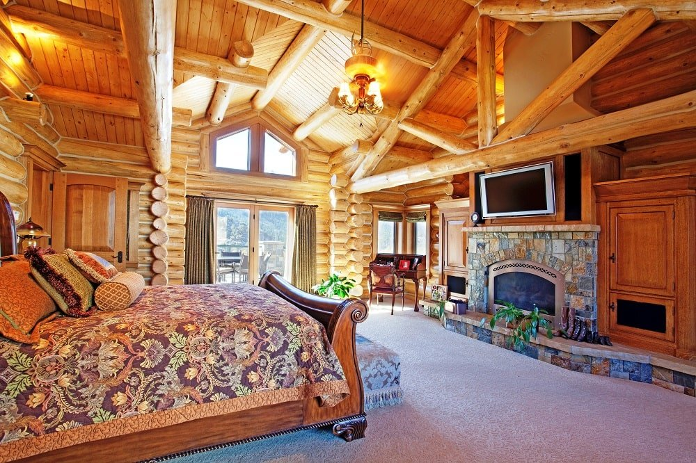 The bedroom also has a tall wooden cathedral ceiling that matches the wooden frame of the sleigh bed across from the stone fireplace topped with a TV. Image courtesy of Toptenrealestatedeals.com.