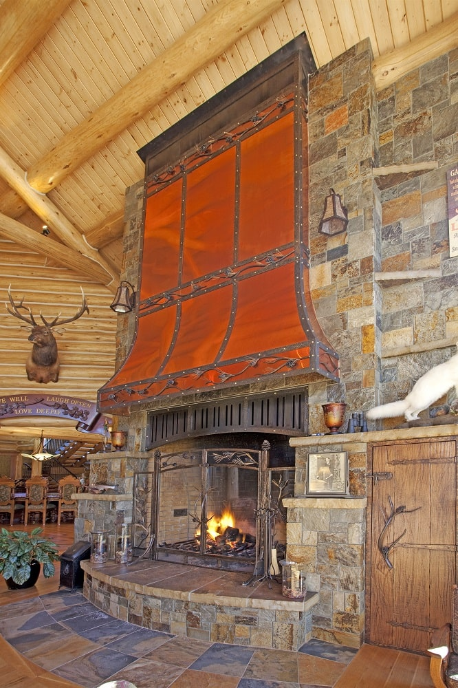 This is a look at the fireplace of the living room with a large stone structure and a copper hood that serves to accent it. Image courtesy of Toptenrealestatedeals.com.