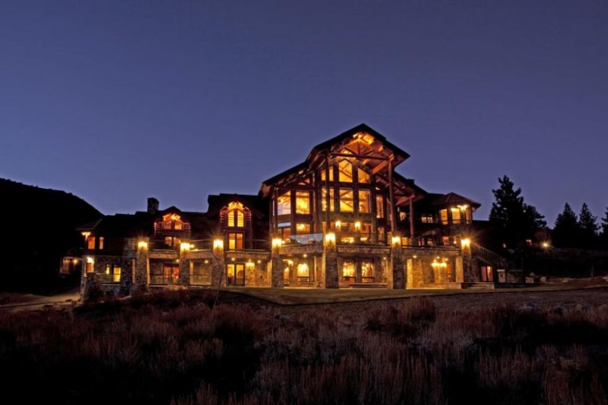 This is the front view of the massive log cabin showcasing the wood and glass exteriors of the house complemented by the warm yellow glow of the interior and exterior lights. Image courtesy of Toptenrealestatedeals.com.