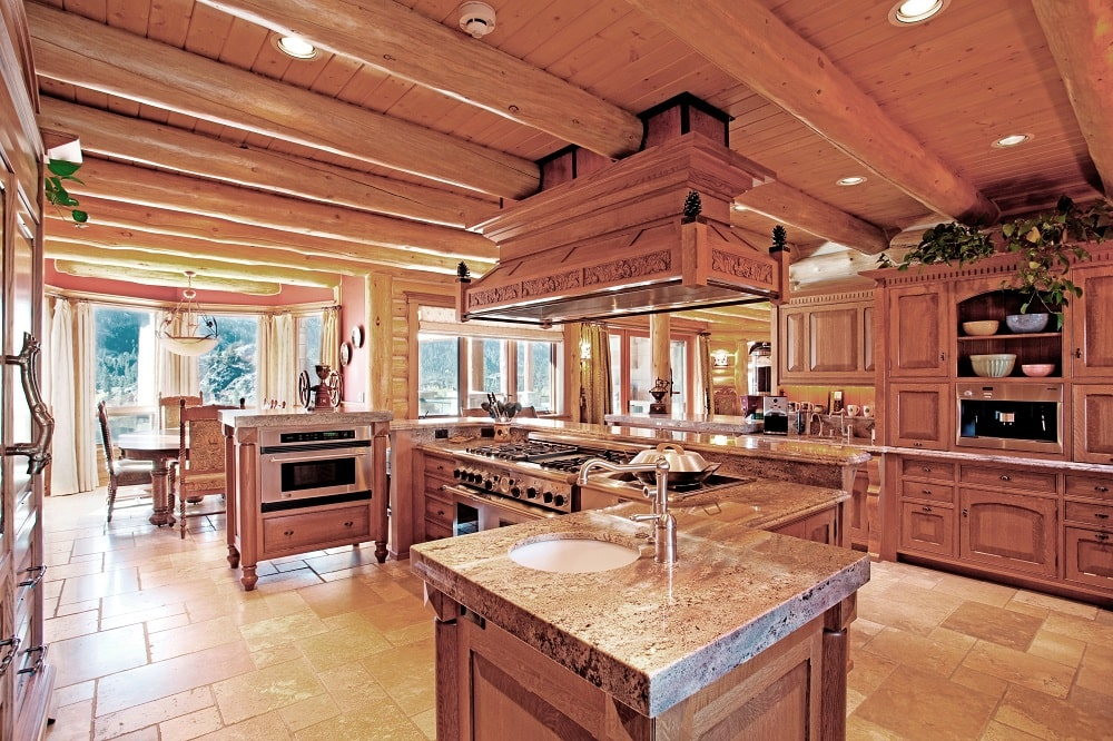 This is the spacious kitchen with a wooden ceiling that has exposed beams and vent hood over the cooking area. The ceiling matches well with the surrounding cabinetry and the kitchen island. Image courtesy of Toptenrealestatedeals.com.