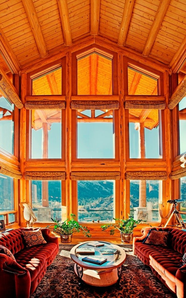 This is the living room with sofas and a coffee table complemented by the tall wooden cathedral ceiling and the large glass wall that affords a scenic view of the mountains. Image courtesy of Toptenrealestatedeals.com.