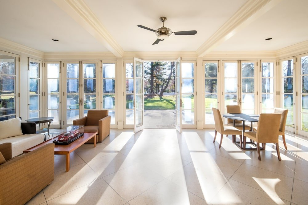 This is the lounge area and breakfast nook complemented by a set of glass doors that fold to open the interior to the outdoor areas. Image courtesy of Toptenrealestatedeals.com.