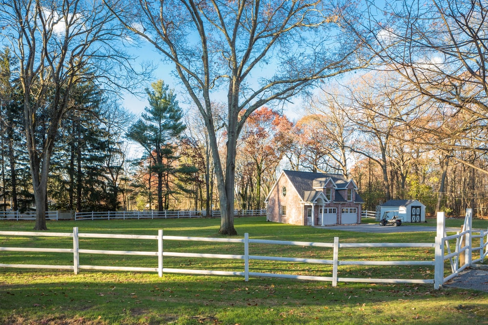 This is a look at the carriage house house in the distance across the landscape of grass lawns and tall trees. Image courtesy of Toptenrealestatedeals.com.
