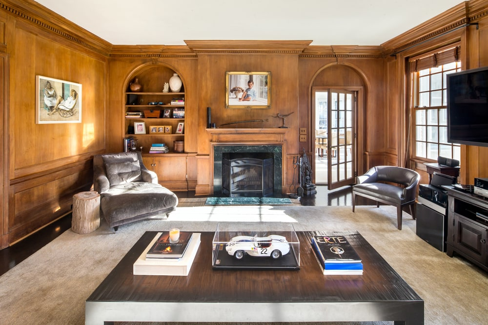 This is the den of the house with mahogany wood paneling on the walls that have built-in bookshelves and archways flanking the fireplace with a wooden mantle on the far side. Image courtesy of Toptenrealestatedeals.com.