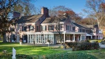 This is a look at the front of the house complemented by the surrounding green landscape of grass lawns and tall trees. You can see here the red brick exterior walls of the house along with various glass windows and a tall chimney in the middle. Image courtesy of Toptenrealestatedeals.com.