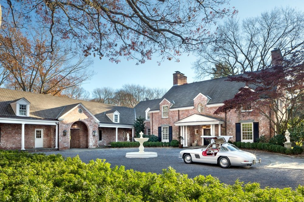 The front of the house has a wide asphalt driveway and a fountain in the middle. Image courtesy of Toptenrealestatedeals.com.