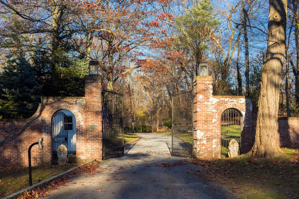 This is a view of the property from the vantage of the main gate. It has a couple of tall red brick pillars supporting the tall wrought-iron gate. Image courtesy of Toptenrealestatedeals.com.