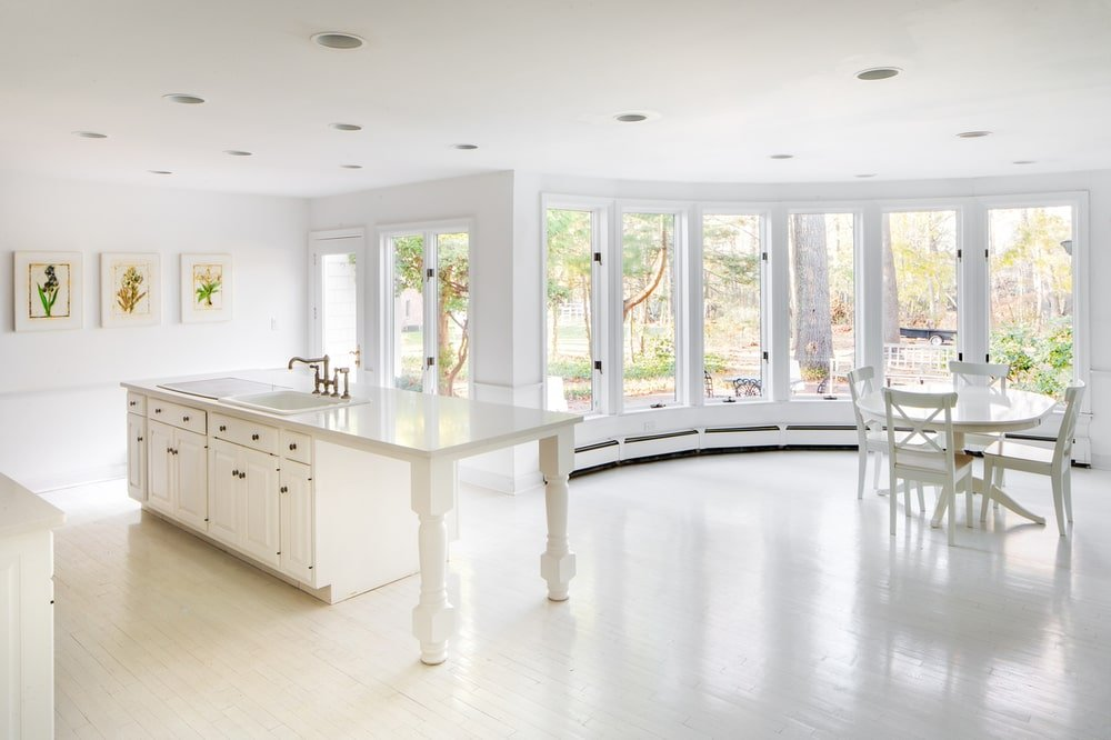 The interior of the guest house shows this bright and light kitchen and informal dining area both bathed in natural lights from the row of windows. Image courtesy of Toptenrealestatedeals.com.