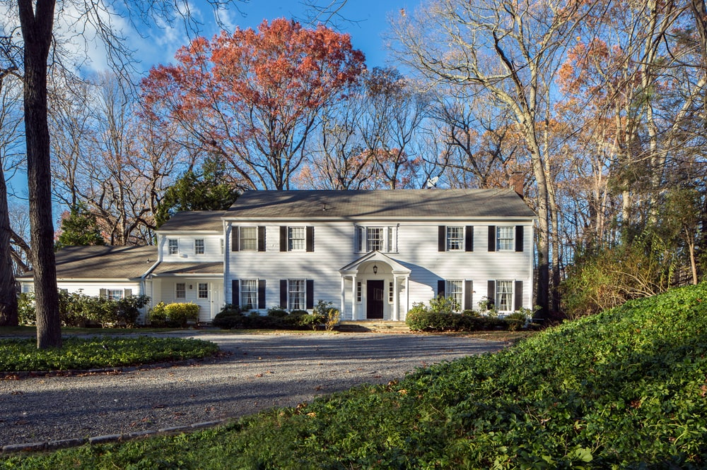 The separate guest house has the same design as the main house in a smaller version adorned by tall trees and shrubs. Image courtesy of Toptenrealestatedeals.com.