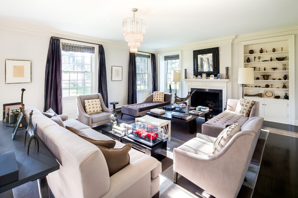 The living room has a large fireplace on the far side of the room with exposed white mantle topped with a painting. across from this is a couple of beige sofas paired with a coffee table. Image courtesy of Toptenrealestatedeals.com.
