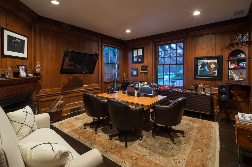 This is the mahogany-paneled home office paired with dark hardwood flooring that blends well with the swivel armchairs surrounding the wooden desk. Image courtesy of Toptenrealestatedeals.com.