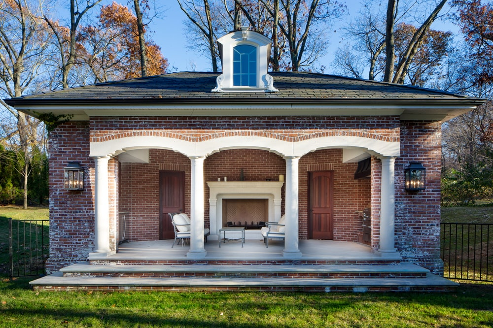 This is the covered patio with red brick walls, arches and pillars that are warmed by the large fireplace with a white mantle. Image courtesy of Toptenrealestatedeals.com.