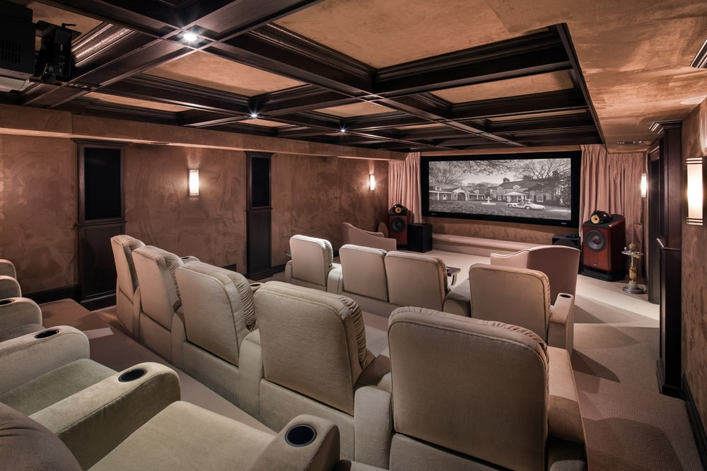 This is the home theater room with a large screen at the far end across from the rows of ascending upholstered theater chairs under a coffered ceiling. Image courtesy of Toptenrealestatedeals.com.