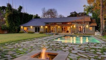 This is a view of the back of the house from the vantage of the pool. You can see here the warm glow of the house from the outdoor lights paired with the glass windows and doors. Image courtesy of Toptenrealestatedeals.com.