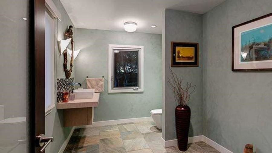 This bathroom has gray walls that make the wall-mounted paintings and mirror stand out. Image courtesy of Toptenrealestatedeals.com.