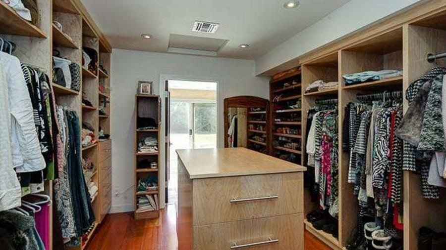 The house also has a spacious walk-in closet with built-in wooden shelves, racks and cabinets on the walls surrounding a small island. Image courtesy of Toptenrealestatedeals.com.