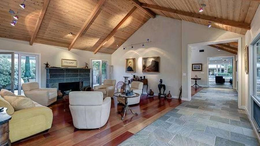 The family room has a large fireplace on the far wall across from the set of sofas and armchairs. Image courtesy of Toptenrealestatedeals.com.